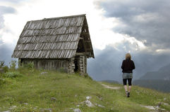 Woman walks to abandoned mountain cottage. Girl exploring abandoned hut in the mountains while storm is approaching Royalty Free Stock Photo