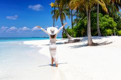 Woman walks on a tropical beach with white hat stock photo