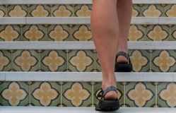 Woman Walks up Patterned Tile Staircase stock image