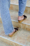 Woman walks up a tiled staircase Royalty Free Stock Image