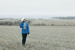 Woman walks in winter field Royalty Free Stock Images