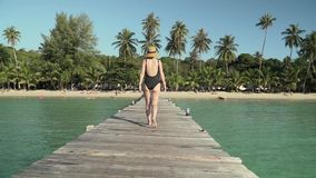 Woman walks on wooden jetty to tropical beach. Young caucasian woman in swimsuit and straw hat happily walks along wooden jetty pier to tropical island coast stock video