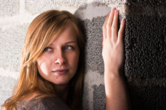 Woman and wall. Portrait of a pensive woman near a wall Stock Image
