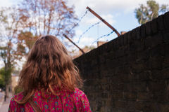 Woman by wall with barb wire Royalty Free Stock Photos