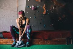 Woman wall climber coating hands with gripping powder. Woman at a wall climbing gym applying magnesium chalk powder on hands from a bag. Artificial bouldering Stock Image