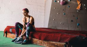 Woman wall climber coating hands with gripping powder. Woman at a wall climbing gym applying magnesium chalk powder on hands from a bag. Artificial bouldering Royalty Free Stock Photo