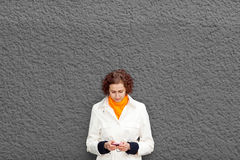 Woman on wall with smartphone. Young woman on grey wall with her smartphone Stock Photography