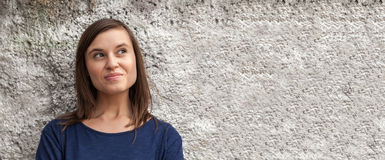 Woman at a wall Stock Images