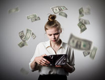 Woman and wallet. Dollars. Worried slim woman is looking in a wallet. Dollars are falling Stock Image