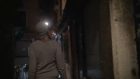 Woman wandering in dark alleyway at night. Slow motion steadicam shot of a woman walking along the alleyway with dim light. Night city with worn grungy buildings stock video