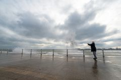 Woman watch and photograph waves and get wet at the black sea. Woman want to see and photograph the waves so close and get wet by the splash waves who turn over royalty free stock photo