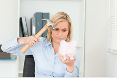 Woman wanting to destroy her piggy bank Royalty Free Stock Images