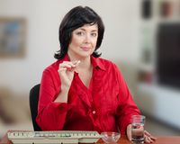 Woman wants take small pill. Woman in red blouse holds white pill and looks at the camera. She intends to take this medicine. The woman sits at the office desk Stock Image