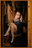 Woman wardrobe. Fashion madness. Expressive woman sitting in the wardrobe with clothes Stock Photos