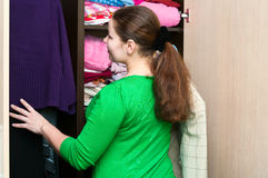 Woman in the wardrobe. Young caucasian woman in the wardrobe packs things on a shelfs Stock Photo