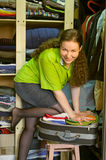 Woman in the wardrobe packs things into a suitcase. By own knee Royalty Free Stock Photos