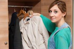 Woman and Wardrobe. Young beautiful woman looking at an empty wardrobe Royalty Free Stock Photography