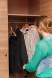 Woman and Wardrobe. Young beautiful woman looking at an empty wardrobe Royalty Free Stock Photos
