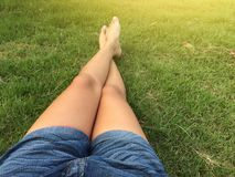 Woman ware short jean sitting on the green grass royalty free stock photo