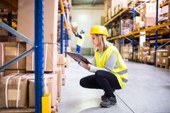 Woman warehouse worker with clipboard. Young women worker or supervisor with clipboard. Warehouse workers controlling stock Royalty Free Stock Photo