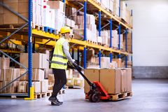 Woman warehouse worker with hand forklift truck. Young woman warehouse worker with hand forklift truck Royalty Free Stock Photography