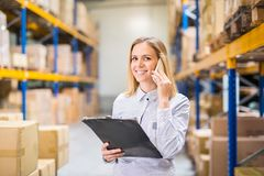 Woman warehouse worker or supervisor with smartphone. Young woman warehouse worker or supervisor with smartphone, making a phone call stock images