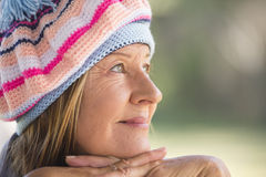 Woman with warm beanie cap winter outdoor. Portrait attractive mature woman with beanie hat to keep warm in winter, friendly laid back smiling, blurred Stock Photo
