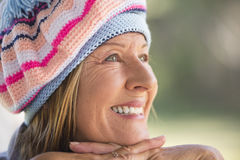 Woman with warm beanie cap winter. Portrait attractive mature woman with beanie hat to keep warm in winter, friendly relaxed smiling, blurred background outdoor Stock Photos