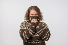 Woman in warm brown sweater hiding her face. Only eyes are seen. She wants to stay anonym. Fear of people and social phobia royalty free stock photography