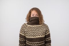 Woman in warm brown sweater hiding her face. Only eyes are seen. She wants to stay anonym. Fear of people and social phobia royalty free stock photo