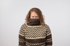 Woman in warm brown sweater hiding her face. Only eyes are seen. She wants to stay anonym. Fear of people and social phobia stock images