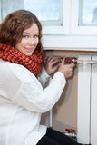 Woman in warm clothes controling temperature of heating radiator Stock Photos