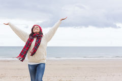 Woman in warm clothing stretching arms on beach Royalty Free Stock Images
