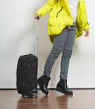 Woman in warm jacket with suitcase. Stock Photo