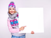 Woman in warm outerwear  holds the banner and points on it Stock Image