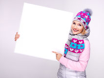Woman in warm outerwear  holds the banner and points on it Stock Photo
