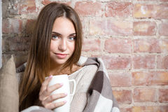 Woman in warm plaid holding cup with hot tea Stock Photo