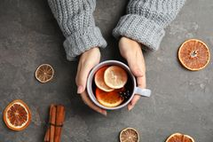 Woman in warm sweater with cup. Of hot winter drink on gray background, top view. Cozy season royalty free stock photography