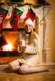 Woman in warm sweater and hat sitting at fireplace with tea cup Royalty Free Stock Photo