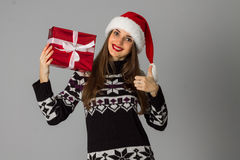 Woman in warm sweater and santa hat with red gift Stock Image