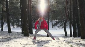 Woman warm up before jogging in cold winter forest. Wearing warm sporty running clothing and gloves. Beautiful fit female fitness model stock video footage