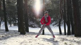 Woman warm up before jogging in cold winter forest. Wearing warm sporty running clothing and gloves. Beautiful fit female fitness model stock footage