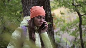 Woman in warm wear talking on cellphone in the autumnal forest. Young woman in warm wear with backpack talking on cellphone in the autumnal forest stock video footage