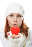 Woman in warm white clothing sends a kiss Stock Images