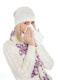 Woman in warm winter clothing sneezing from cold Royalty Free Stock Images