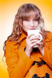 Woman in warm winter coat sipping hot coffee. Woman in a warm winter coat sipping and savouring a mug of hot steaming coffee or soup which she is nurturing in Stock Photos