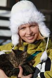 Woman in warm winter jacket with cat in hands Royalty Free Stock Photos