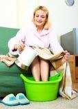Woman warming feet in basin Stock Image