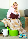 Woman warming feet and reading Royalty Free Stock Image