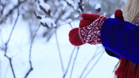 Woman warming frozen hands in mittens stock footage
